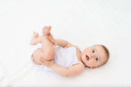 baby girl 6 months old lying in a crib in the children's room on her back and holding her legs, looking at the camera, baby's morning, baby products concept Standard-Bild