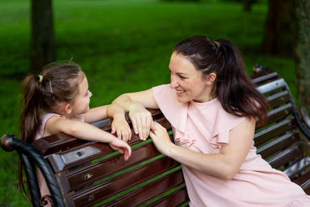 mother and daughter 5-6 years old walking in the Park in the summer, daughter and mother laughing on a bench, the concept of a happy family, the relationship of mother and child, mother's day 免版税图像