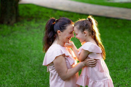 mother and daughter 5-6 years old walking in the Park in the summer, daughter and mother laughing on a bench, the concept of a happy family, the relationship of mother and child, mother's day 스톡 콘텐츠