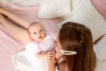 mother feeds baby 6 months of breast sitting on a white bed at home, place for text Stock fotó