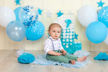 Baby boy celebrates 1 year with cake and balloons, happy childhood, children's birthday Imagens