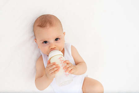 baby boy 8 months old lying on the bed in the nursery on his back and holding a bottle of milk, feeding the baby, baby food concept