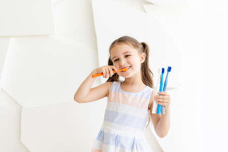 little girl brushing her teeth on a white background and holding toothbrushes, place for text, healthy teeth
