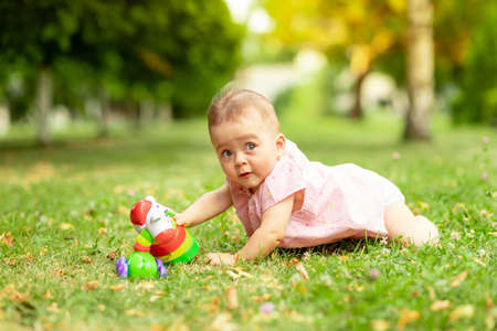 little baby girl 7 months old playing on a green lawn in a pink bodysuit, walking in the fresh air, early development of children up to a year