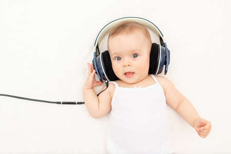 small baby girl 6 months old lying on the bed with headphones and listening to music, place for text, top view