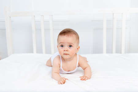 smiling baby girl 6 months old lies on the bed in the nursery on her stomach and looks away, morning baby, baby products concept Standard-Bild