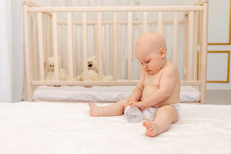 baby boy 8 months old sitting in diapers on a white bed with a bottle of milk at home, baby food concept, first bait, place for text
