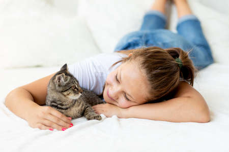 A child is torturing an animal, a little girl with a cat is lying on the bed, the concept of a child's friendship with animals