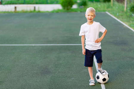 a blond boy in a sports uniform stands on a football field with a soccer ball, sports section. Training of children, children's leisure.