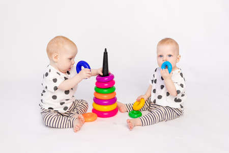 two twin babies 8 months old play on a white isolated background, early development of children up to a year old, a child takes a toy from another, a place for text