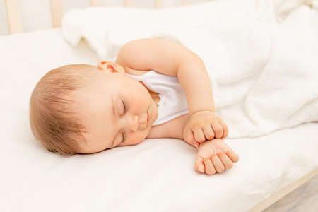 Small baby girl 6 months old sleeping in a white bed, healthy baby sleep