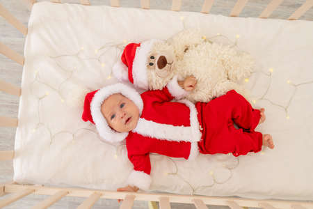 Christmas photo of a baby in a Santa suit lying in a crib at home, top view, happy new year. Christmas holiday concept Foto de archivo