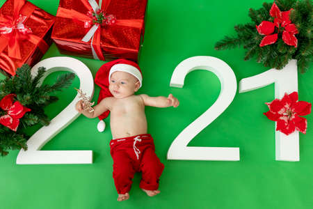 a 6 month old baby in a Santa costume lies on a green isolated background with the inscription 2021 and gifts