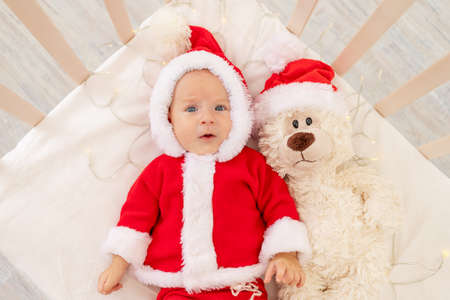 Christmas photo of a baby in a Santa costume lying in a crib at home with a toy in a Santa Claus hat, top view, happy new year. Foto de archivo