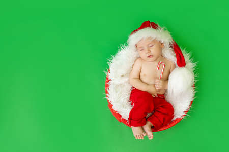 a sleeping child in a Santa costume lies with a candy in his hands on a green isolated background, waiting for the new year and Christmas, space for text Archivio Fotografico