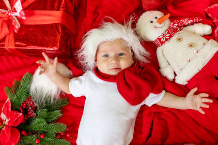 a funny child in a Santa costume lies on a red background among gifts, a Christmas tree and a snowman waiting for the new year and Christmas, space for text Archivio Fotografico