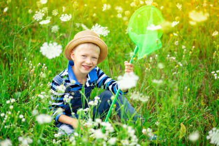 a happy boy in a hat walks through a field with flowers and catches butterflies with a net, happy childhood, children's lifestyle Foto de archivo