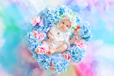 beautiful baby 6 months in a hat made of flowers, lying in a basket with hydrangeas on a blue background, a small child among flowers