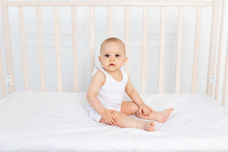 Baby boy 8 months old sitting in a crib in a children's room in white clothes and looking at the camera, the morning of the baby