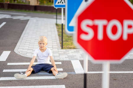 a child is sitting on the road at a pedestrian crossing among road signs, traffic rules for children Stock Photo