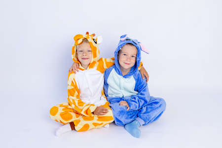 little boys brothers in fun bright costumes sit on a white isolated background, children's birthday, place for text