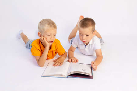 two preschooler brother boys lie on a white isolated background and read a book, a place for text