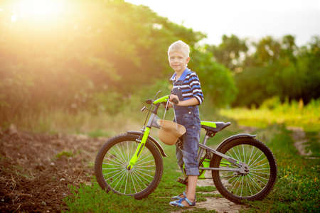 happy baby boy blond with a Bicycle stands in a field in summer, children's lifestyle Zdjęcie Seryjne