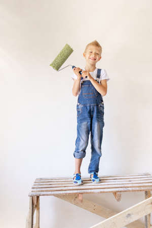 a blond child stands on a construction ladder in an apartment with white walls and a roller in his hands, a place for text, the concept of repair