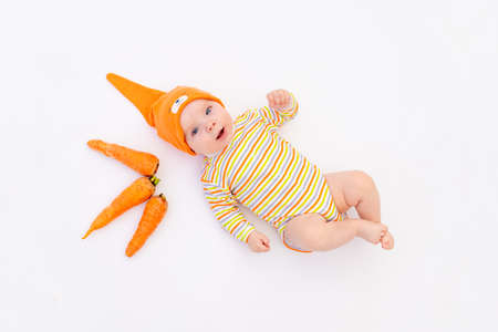 small baby girl lying on a white isolated background with a carrot, space for text, baby food concept