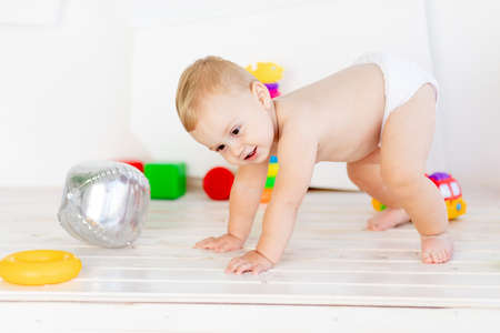 a small child a boy six months old tries to get back on his feet in a light white nursery in diapers among toys