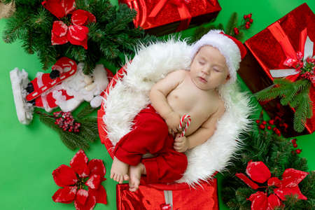 a sleeping child in a Santa costume lies with a candy in his hands on a green isolated background among gifts and Christmas trees, waiting for the new year and Christmas