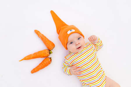 small baby girl 6 months old lying on a white isolated background with a carrot, space for text, first complementary food, baby food concept Фото со стока