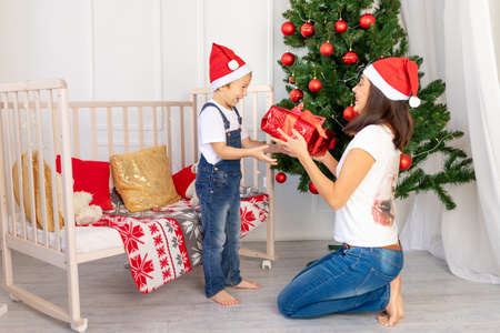 mom gives a child a gift in a large red box for new year or Christmas in the children's room with a new year's interior near the Christmas tree