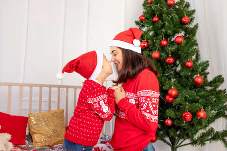 mom kisses a child in red sweaters before new year or Christmas in the children's room near the Christmas tree