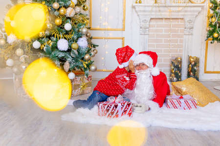 a child whispers to Santa Claus in the ear near the Christmas tree in the yellow and white Christmas interior, a happy child talks to Santa Claus