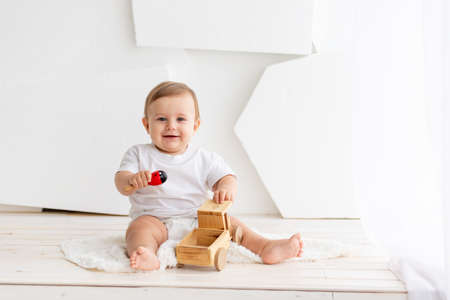happy cute little baby six months old in a white t-shirt and diapers sits on a light background at home and plays with a wooden typewriter, space for text Stockfoto