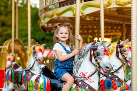 happy baby girl rides a carousel on a horse in an amusement Park in summer 스톡 콘텐츠
