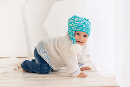 a small child six months old in a knitted warm jacket and hat is crawling at home in a bright room