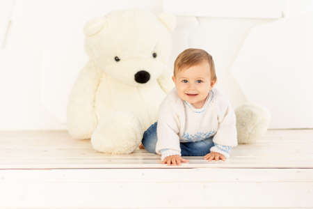 a happy little child six months old in a knitted warm jacket and blue jeans crawls at home near a large Teddy bear Reklamní fotografie