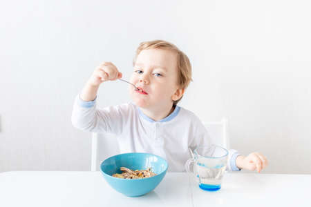 baby boy eats with a spoon at home, the concept of food and nutrition for children