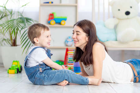the mother talks to the baby boy or plays at home with educational toys in the children's room. A happy, loving family.