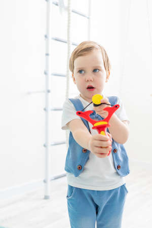 the kid with the slingshot at home, sweet boy shoots a slingshot