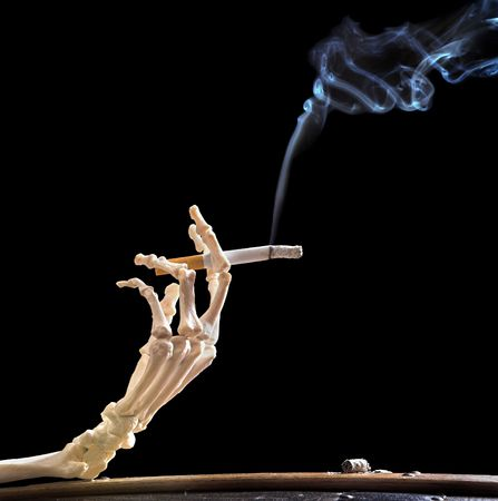 skeleton hand: Hand of death holding a smoking cigarette