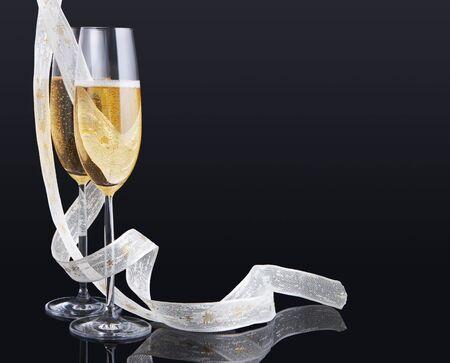 Elegant champagne glasses and a white christmas ribbon