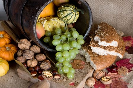 Antique bucket filled with autumn products, and traditional bread on a wooden board Stock Photo - 3707478