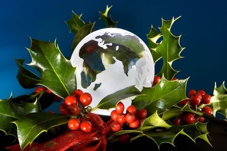 Glass globe lit from below, decorated with christmas holly