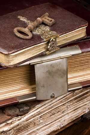 Old key lying on antique books with locks Stock Photo