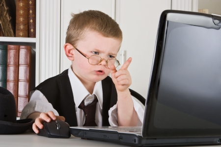 Four year old boss playing director and looking at his computer screen Stock Photo