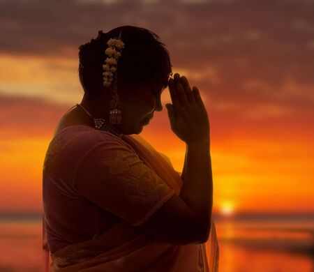 Indian lady in saree doing the namaste greeting at sunset Stock Photo - 3705555