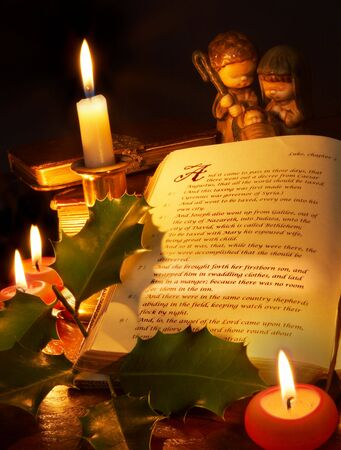 The story of christmas highlighted in an old bible, with candles